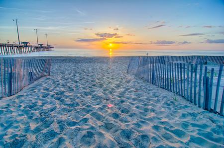 nags: El sol asoma entre las nubes y se refleja en las ondas por el muelle de pesca Nags Head en los Outer Banks de Carolina del Norte