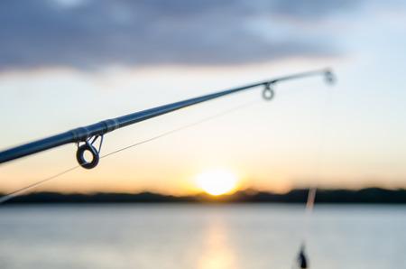 la pêche sur un lac avant le coucher du soleil Banque d'images