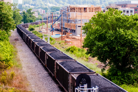 goods train: slow moving Coal wagons on railway tracks Stock Photo