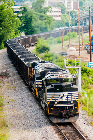 goods train: slow moving Coal wagons on railway tracks Editorial
