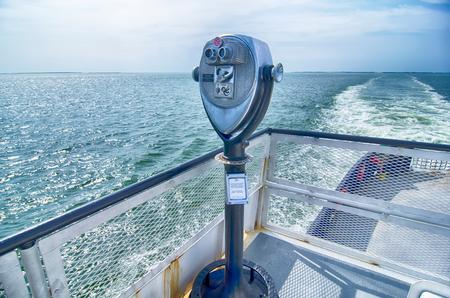 deckled: Binoculars watching at horizon on ship deck