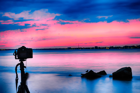 photography session: Dslr camera shooting on a beutiful seascape with blue red sky Stock Photo