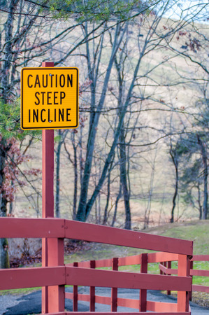 incline: caution steep incline warning yellow sign