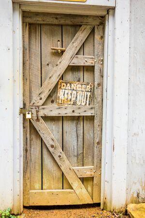rustiness: old wooden door with danger sign