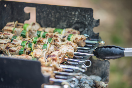 barbequing: steak shishkabob skewers with vegitables cooking on flaming grill