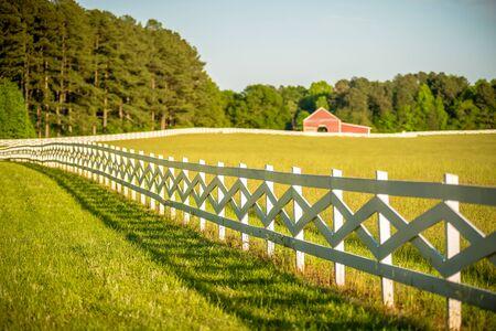 cerca blanca: valla blanca que conduce a un granero rojo grande Foto de archivo