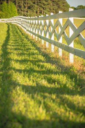 red barn: white fence leading up to a big red barn