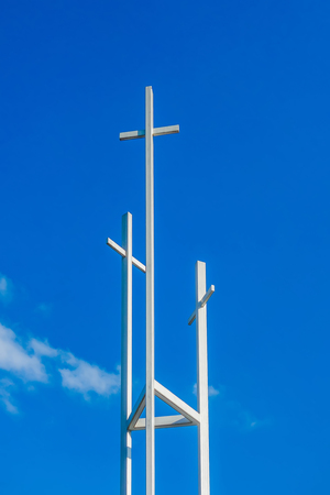 hope symbol of light: Three trinity White Christian crosses in front of a cloudy sky with copyspace Stock Photo