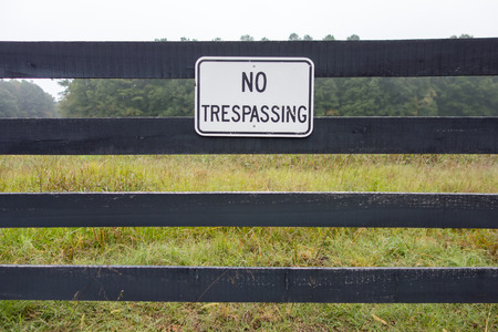 No trespassing sign against backdrop of farmland