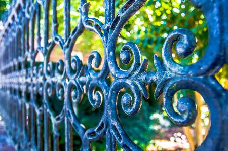 クラシックなデザインの黒鍛造鉄門、美しい緑豊かな庭園 写真素材
