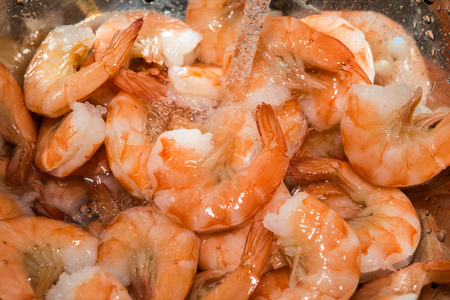 rinsing: rinsing cooked shrimp in sink with water
