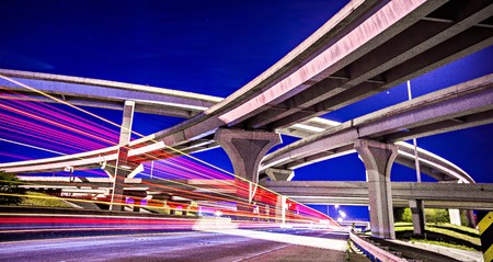night traffic with light trails on highway interchange