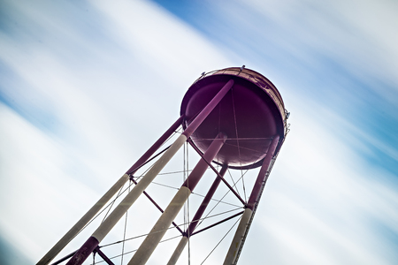 abandoned factory: Long exposure sky and clouds with water tower Stock Photo