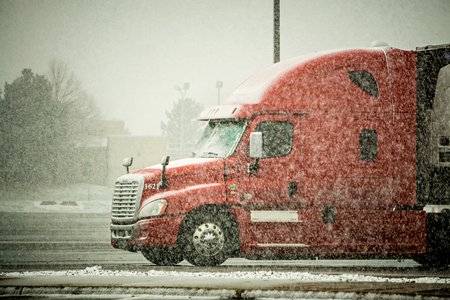 semi truck hauler driving through blizzard snow conditions weather