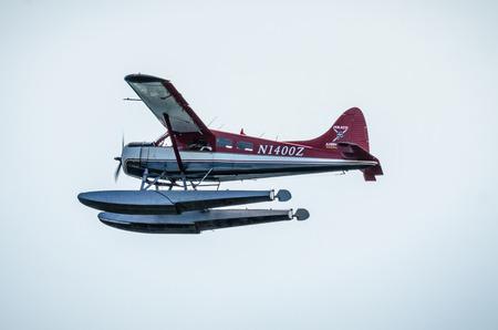 Single Prop Airplane Pontoon Plane flying in alaska mountains