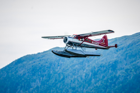 Single Prop Airplane Pontoon Plane flying in alaska mountains