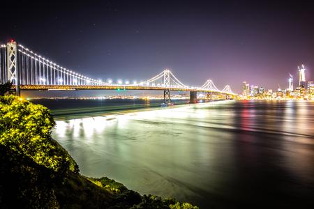 oakland bay bridge in california at night with san francisco skyline