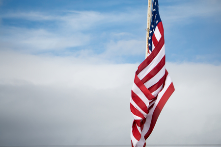 american flag flying on blue sky background