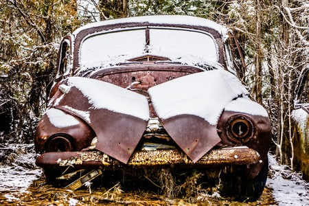 old vintage plymouth automobile in the woods covered in snow Stock Photo