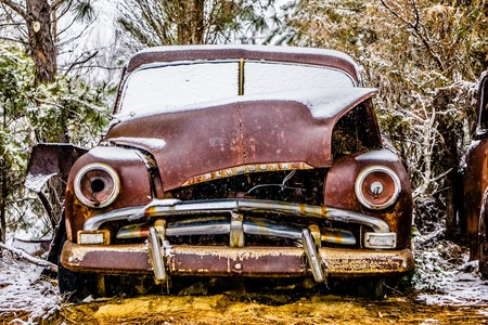 old vintage plymouth automobile in the woods covered in snow 스톡 콘텐츠