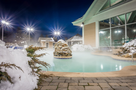 hot tubs and ingound heated pool at a mountain village in winter at night Zdjęcie Seryjne - 100987211