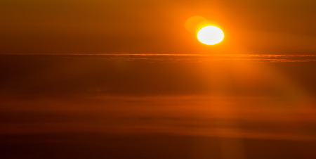 sunset or sunrise from an airplane peeking through the clouds Stock Photo