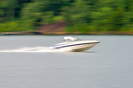 abstract blur of nature and fast moving boat on lake