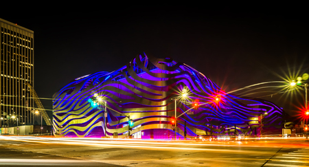 Exterior of Petersen Automotive Museum at night in november with car trails