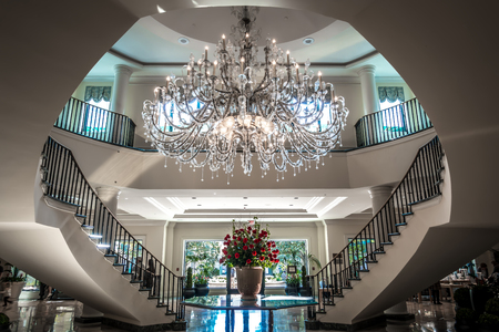 Chandelier hanging over lobby with stair and luxury hall
