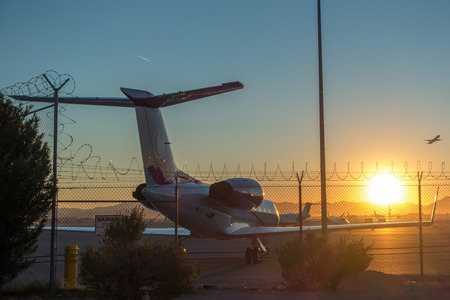 sunrise at the airport with barbed wire security fence and jetlined