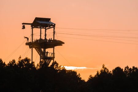 zipline tower with people silhouettes at sunset