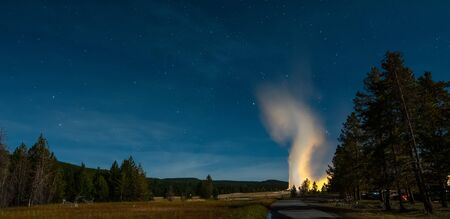 Eruption of Old Faithful geyser at Yellowstone National Park at night Imagens