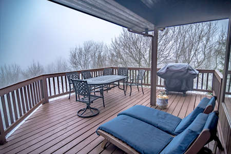furniture on log cabing porch high in the mountains with fog outside