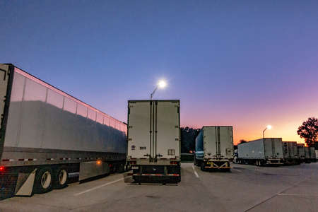 big rig semi trucks and trailers at rest area at sunrise