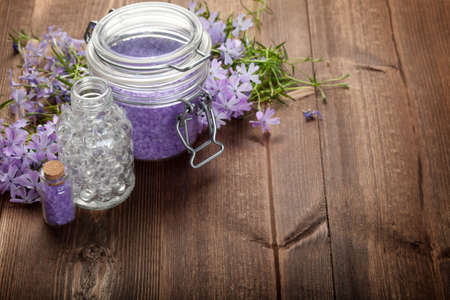 Spa minerals and flowers on wood background photo