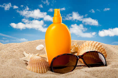 Zonnebrandolie en donkere bril op het strand Stockfoto