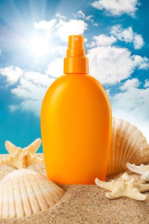 Suntan oil and sea shells photo