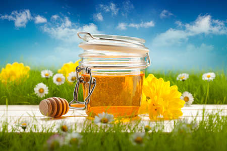 Jar of honey and spring flowers  photo