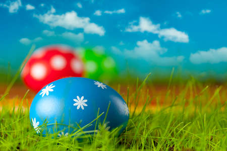 Colored Easter eggs on the grass and blue sky background photo