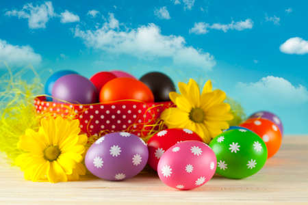 Colored Easter eggs on blue sky background photo