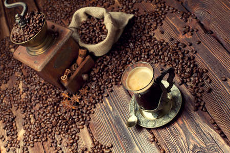 Coffee cup and beans, old coffee grinder and canvas sack photo
