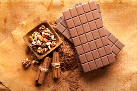 sweetmeats: Four chocolate bars, cinnamon sticks, cocoa and mixed nuts in a bowl Stock Photo