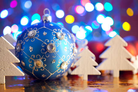 goody: Blue Christmas bauble and white trees on colored background