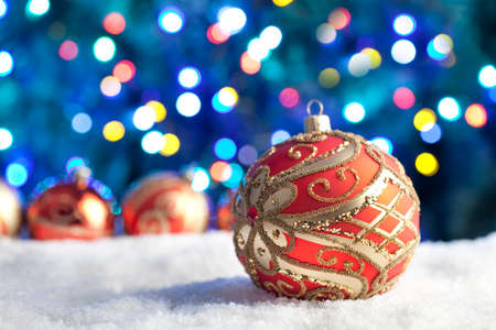 goody: Red Christmas baubles on snow and lighting background Stock Photo