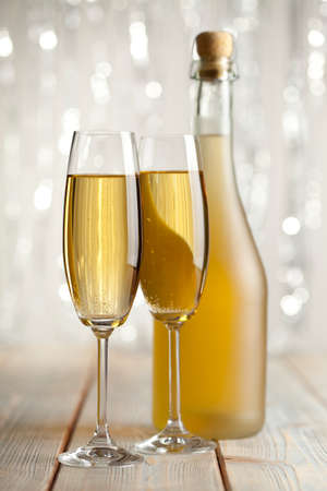 silver flute: Two glasses and bottle of champagne on shining background Stock Photo