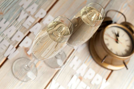 silver flute: Glasses of champagne and alarm clock on wooden background