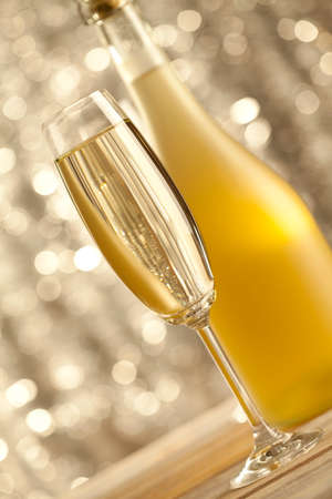 gold flute: Glass and bottle of champagne on bokeh background