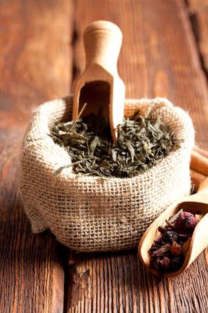 sacco juta: Foglie di tè in sacco di juta su tavola di legno