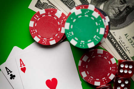 Poker chips, dices and playing cards on green table