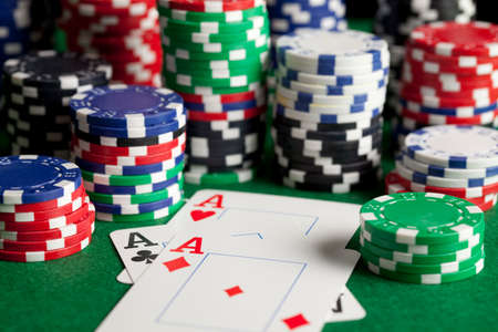Playing cards and poker chips on green table Stock Photo